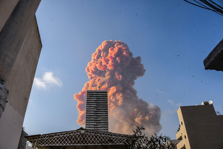 A large plume of smoke can be seen behind a building reaching into the air