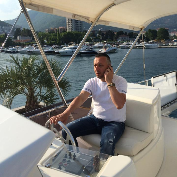 A man sits on a boat with a phone up to his ear