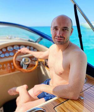Новиков сидит за штурвалом роскошного катера