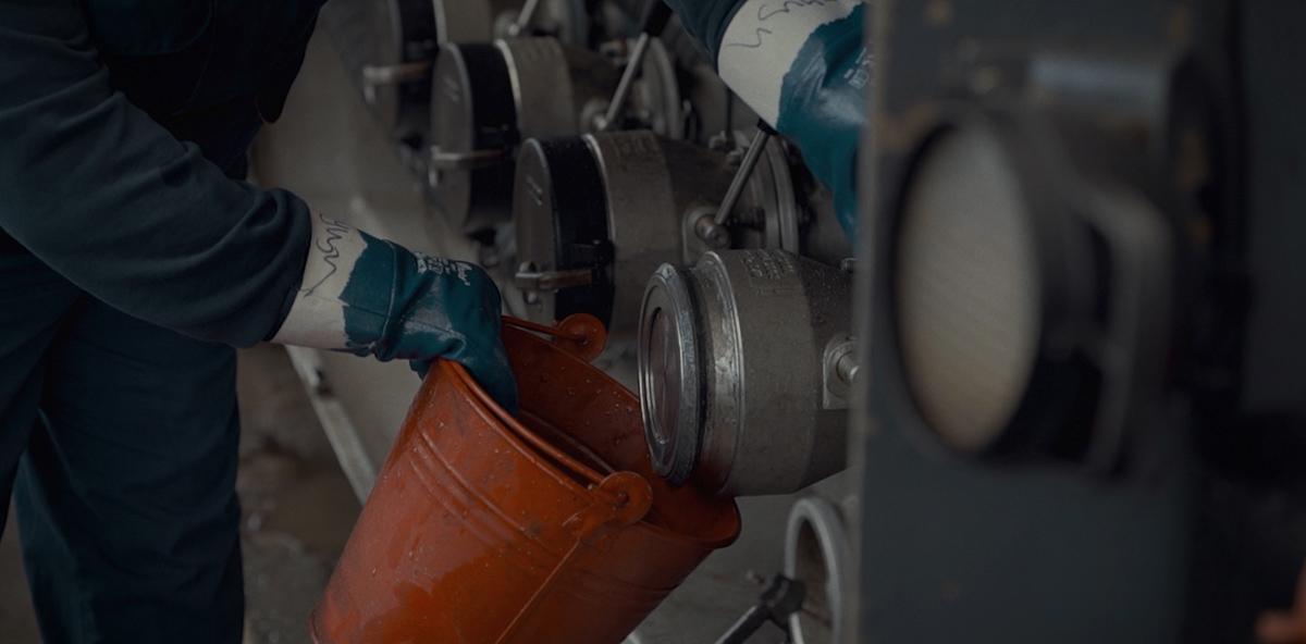 Ein Arbeiter sammelt mit einem Eimer eine Ölprobe.