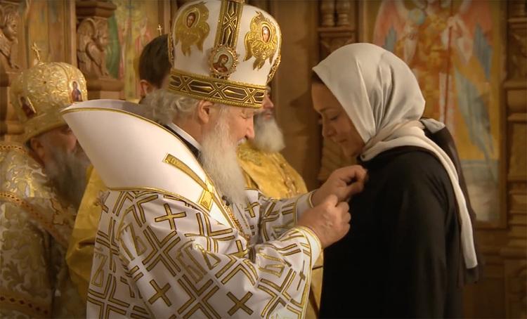 Показано, как Полякова получает награду Патриарха Кирилла.