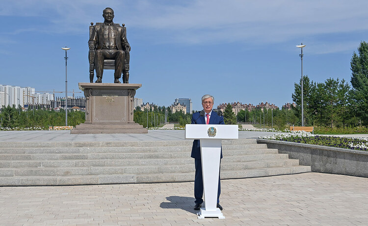 Tokayev stands at a podium in front of a monument