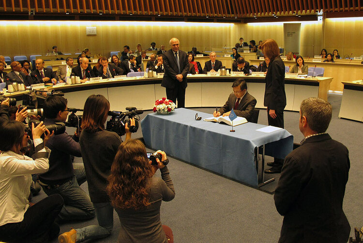 A man signs a treaty while others look on