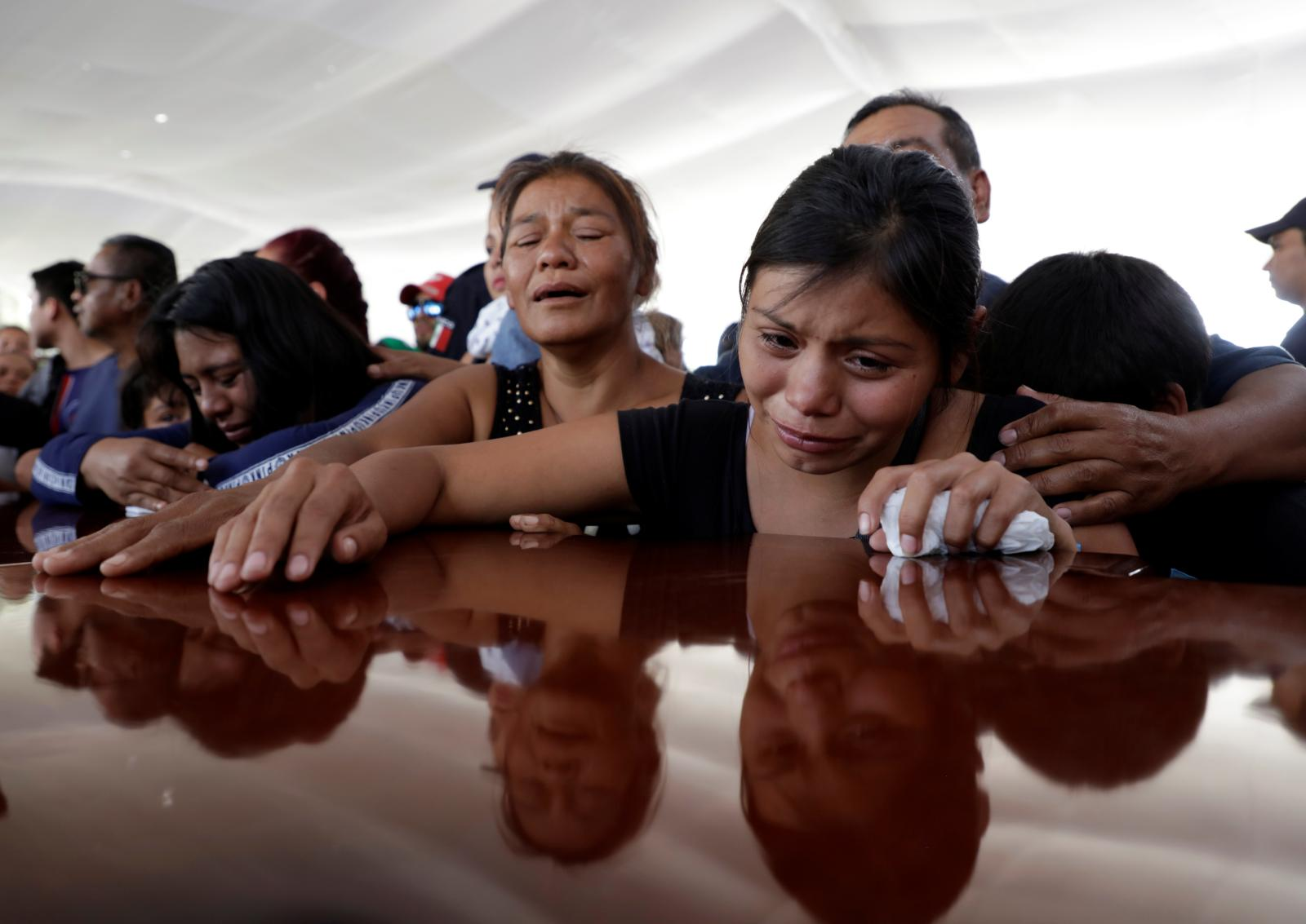 Relatives of a police officer, who was killed along with other fellow police officers during an ambush by suspected cartel hitmen, react during an homage organised by the state government, in Morelia, in Michoacan state, Mexico October 15, 2019. REUTERS/Alan Ortega