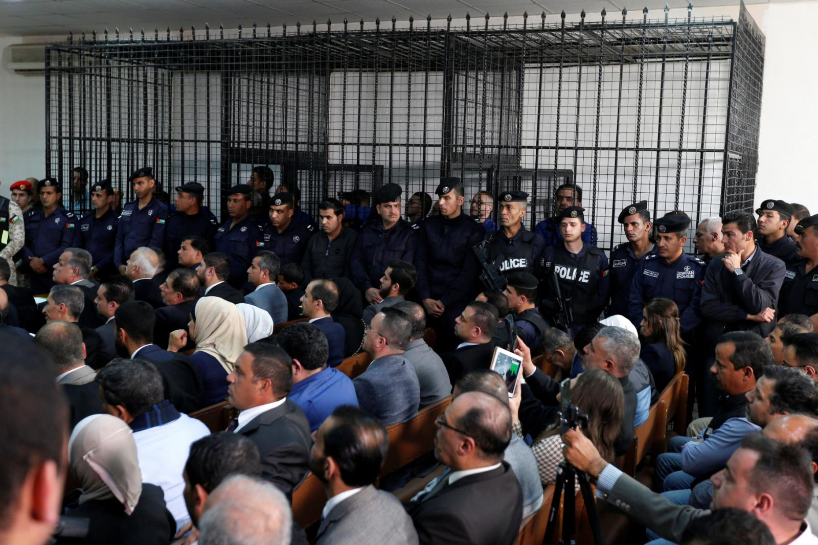 The businessmen and customs officials charged with tax evasion are seen behind bars at the State Security Court in Amman, Jordan, on March 12, 2019. REUTERS/Muhammad Hamed