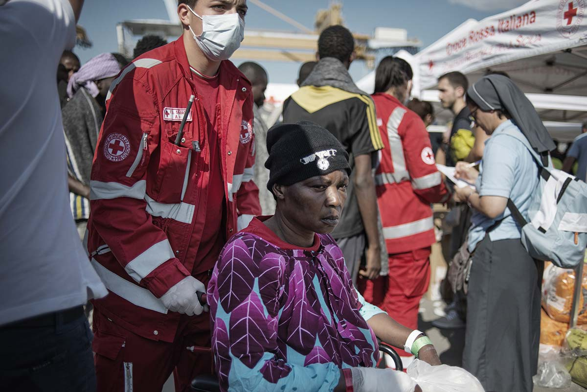 An exhausted asylum seeker pushed in a wheelchair at the port in Palermo (Photo: Valentino Bellini)