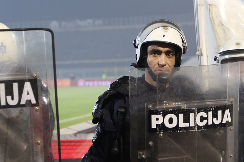 A riot policeman stands guard at a Belgrade football match (Photo: Aubrey Belford)
