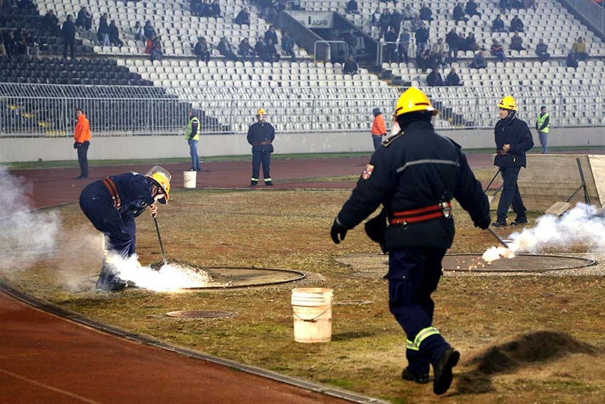 Firemen extinguish flares thrown onto the field by FK Partizan supporters (Photo: Aubrey Belford)