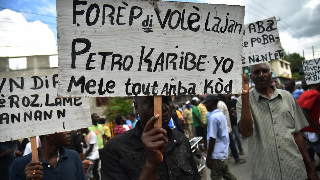 Demonstrators hold up signs about the plundering of the Petrocaribe funds on August 19, 2018 (MedyaLokal, CC BY-SA 4.0)