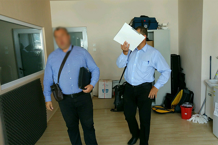 Offices from the Romanian Anti-Fraud Authority at the offices of RISE Project, OCCRP's Romanian partner, during a surprise inspection. (Photo: RISE Project)