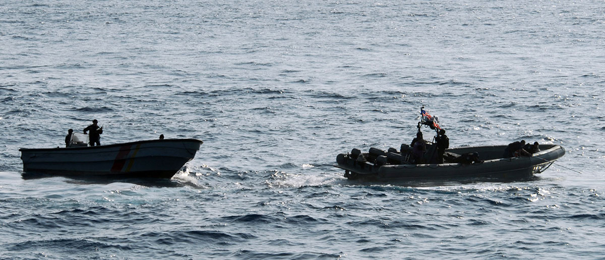 "Colombian navy sailors in a patrol boat, left, and Sailors and Coast Guardsmen from the littoral combat ship USS Freedom search for illicit drugs dumped overboard by the crew of a high-speed ""go-fast"" vessel. (Photo: US Navy)"