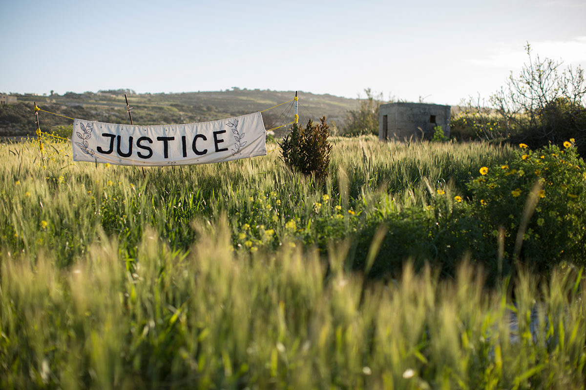 A banner in the fields outside Bidnija, where investigative journalist Daphne Caruana Galizia was murdered six months ago. Photo (c): Dan Kitwood