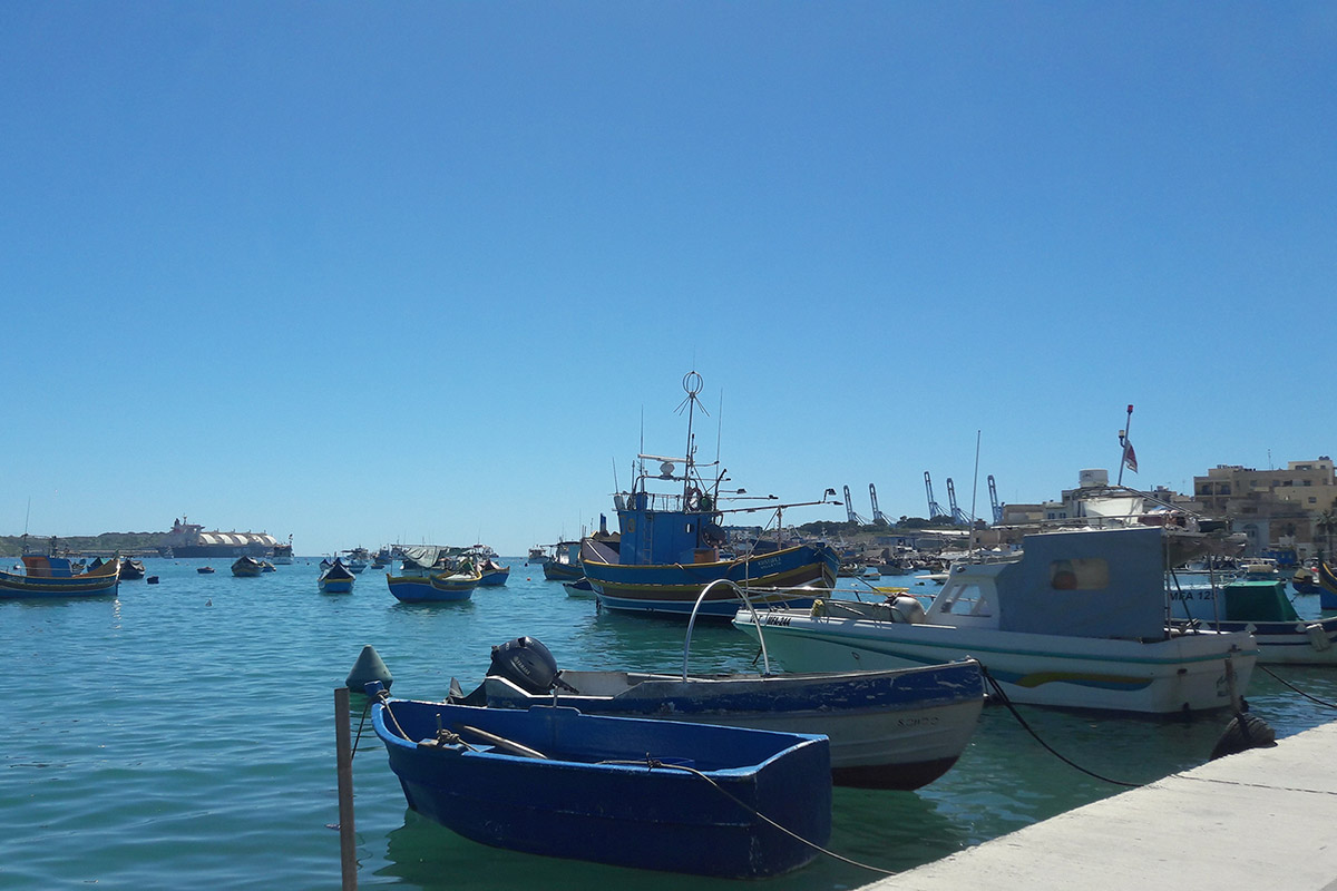 Fishing boats in Marsaxlokk harbor, Malta, with a view of the Delimara power station.