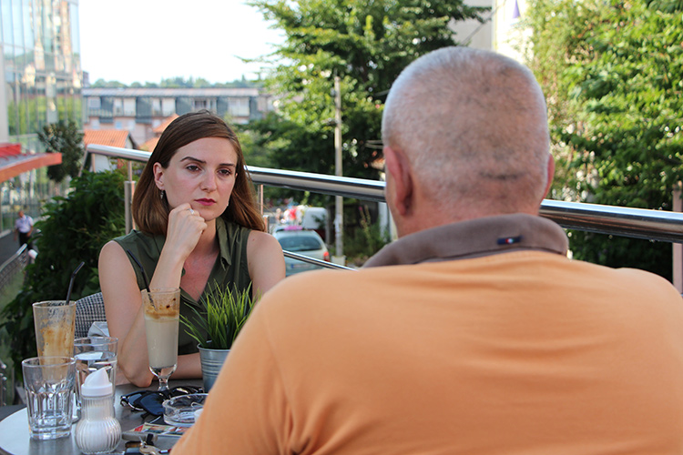 "KRIK reporter Dragana Peco speaks with V.B., a victim of the ""stolen car 'finders,'"" who did not want his identity revealed for fear of retribution. (Photo: KRIK)"