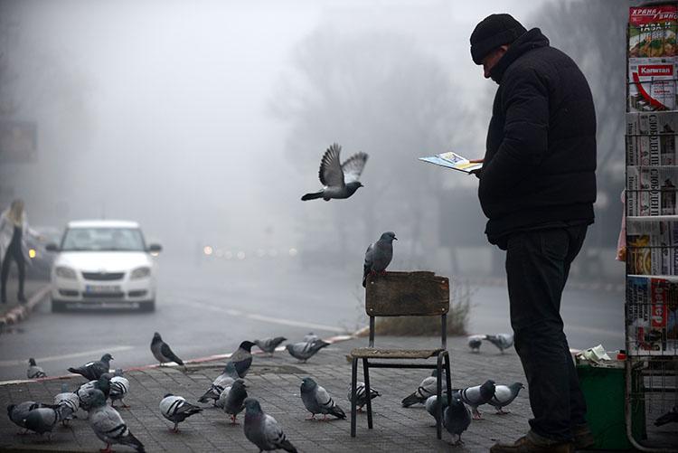 A man reads a magazine near a newsstand in Skopje, Macedonia, 2017.
