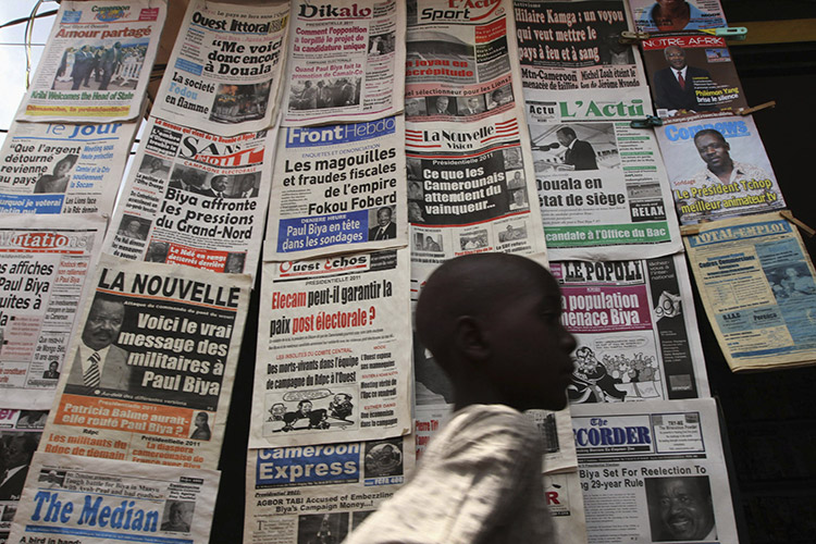 A boy walks past a newspaper kiosk in the Wada district of Cameroon's capital of Yaounde, in the run-up to the presidential elections of October 2011. Photo (c): Reuters / Akintunde Akinleye