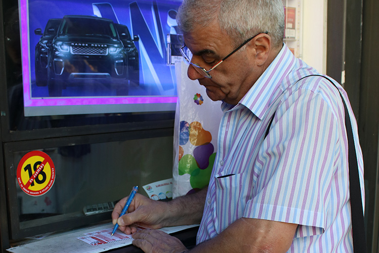 Sporadic lottery player David Pantsulaia, 65, buys a Georgian lottery ticket at a kiosk on Chavchavadze Avenue in Tbilisi. He says he dreams of winning the jackpot. (Photo: Tatuli Omiadze, iFact.ge)