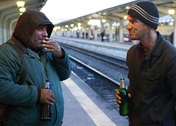 Two men drink beer at a railway station in Romania's capital, Bucharest.