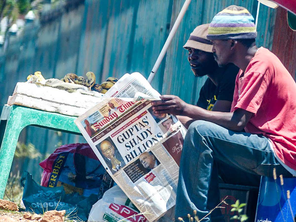 Two South African men read a newspaper detailing another financial scandal involving the Gupta family, October 2016 (the month when South Africa's minister of justice stated in court documents that the brothers were involved in suspicious transactions to the tune of several billion Rand). Photo CC BY-NC-ND 2.0: Skatkat / Flickr. Some rights reserved.]